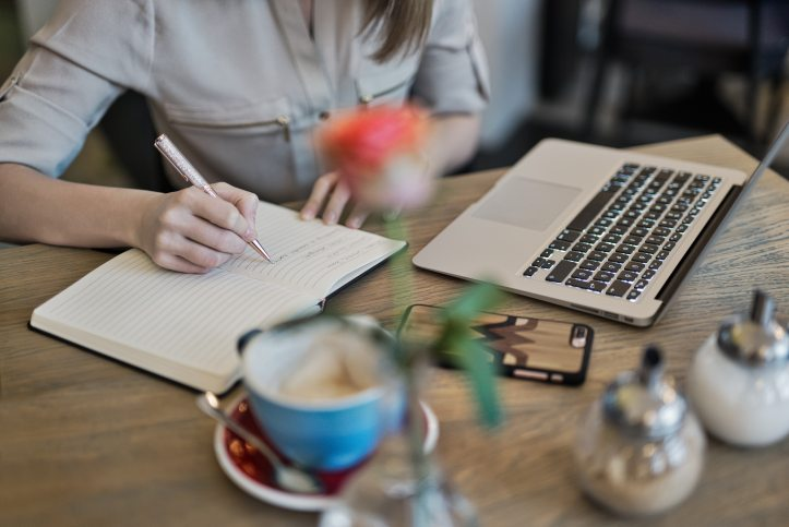 writer writing in a notebook with laptop